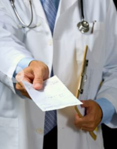 Picture of doctor handing a patient a script